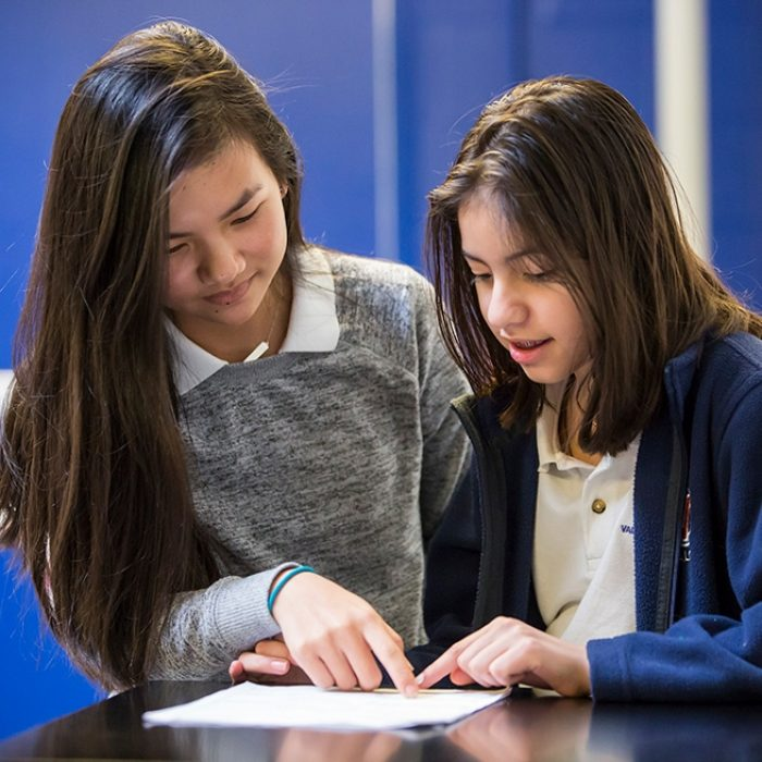 Two students look down together at a paper on desk