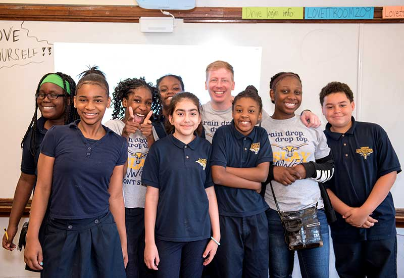 Eight students stand with teacher in front of white board, smiling