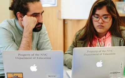 Teacher and student speaking, working on laptops