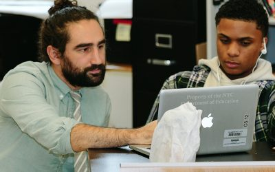 Teacher and student look at the same laptop