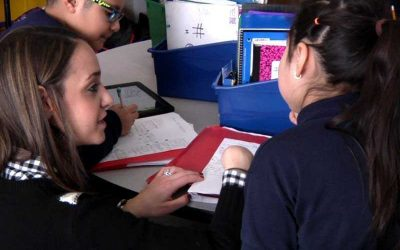Photo of teacher working with two students
