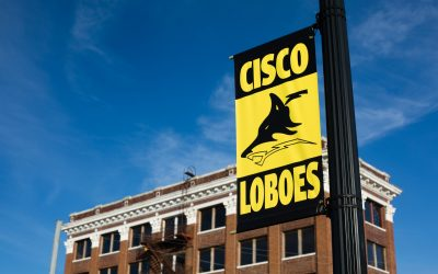 "Outdoor view of school building, with a yellow and black sign reading ""Cisco Loboes"" in the foreground, showing the school's mascot"