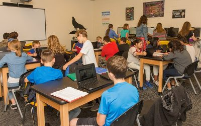 Wide view of classroom setup as students sit grouped in desk arrangements