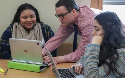 Photo of teacher working with two students on their laptops