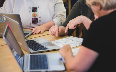 Teachers point at paper while working off of laptops