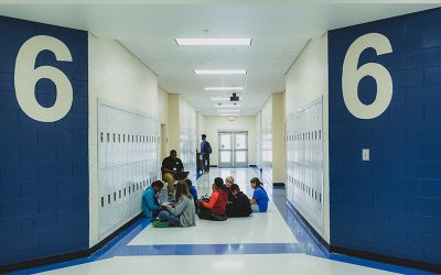 View of teacher sitting in hallway with group of students