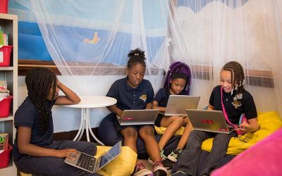 Four female students sit on floor, bean bag chairs while working on laptops