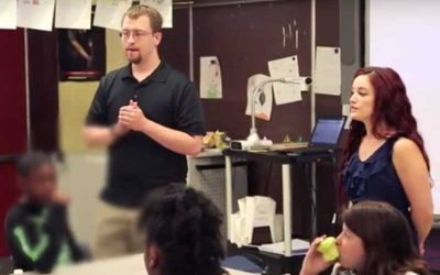 Photo of two teachers standing in front of seated students in a classroom