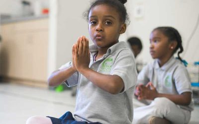 Photo closeup of student with hands together at heart center for mindfulness