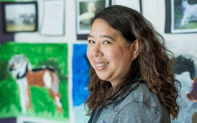 Teacher smiles at camera with student artwork on display in background