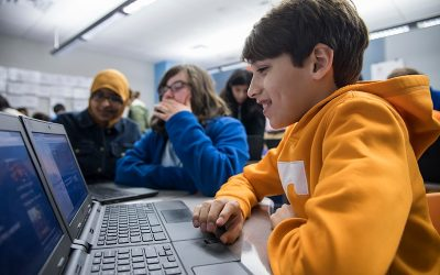 Student smiles as he works on laptop with classmates in background