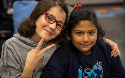 Two students, one showing a peace sign, draping her arm around another student's shoulders