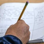 Photo close up of notebook with person making notes in pencil
