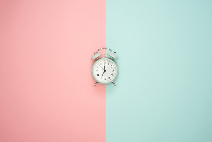 An alarm clock sits on top of a two-toned background, with pink on the left, blue on the right