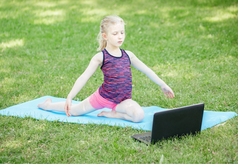 Student exercises on yoga mat outside in front of laptop