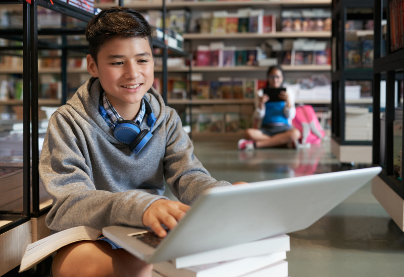 Student sits on floor with laptop stacked on top of books, smiling, typing; another student is visible in the background using a tablet