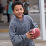 Child runs forward, carrying football