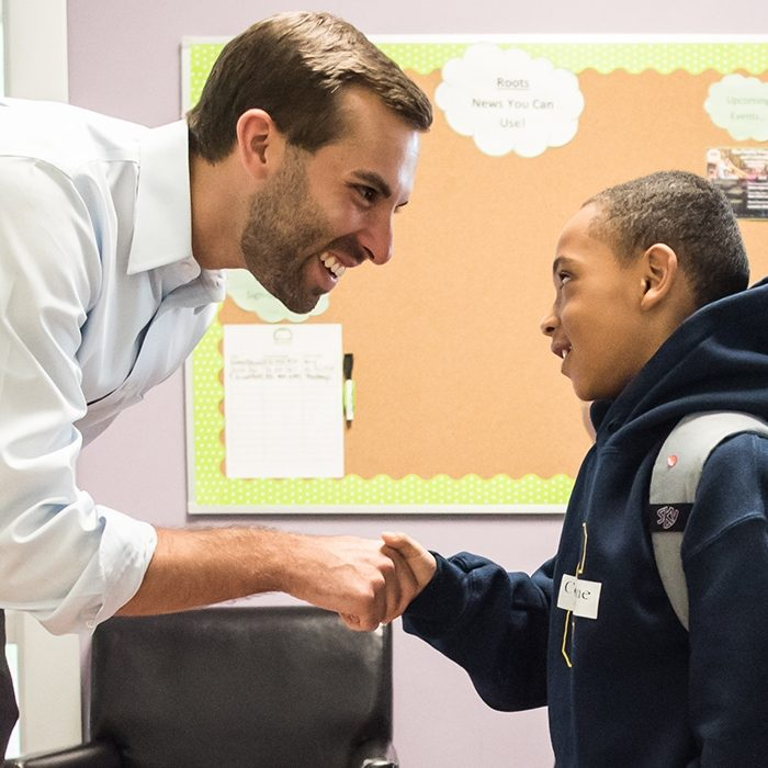 Teacher leans down and shakes child's hand, both smiling