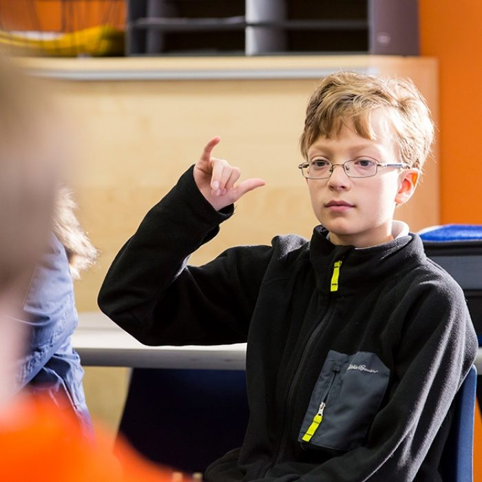 Student sits in classroom, making a gesture of agreement