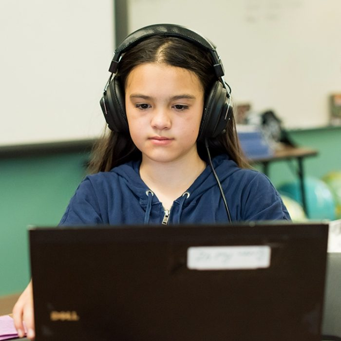 Student looks down at laptop, wearing headphones, smiling
