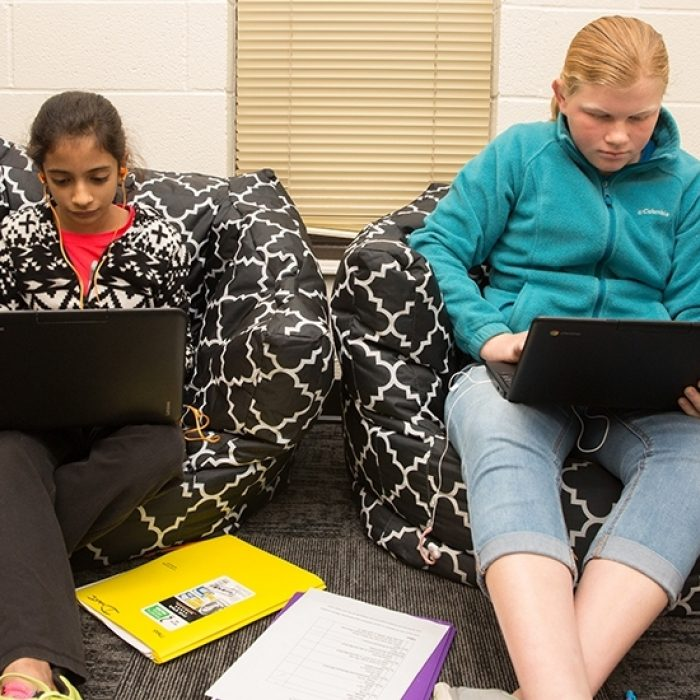 Two students sit side-by-side on beanbag chairs, looking down at laptops