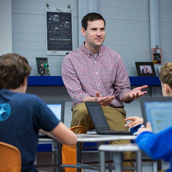 Teacher sits along desk, gesturing to students at desks
