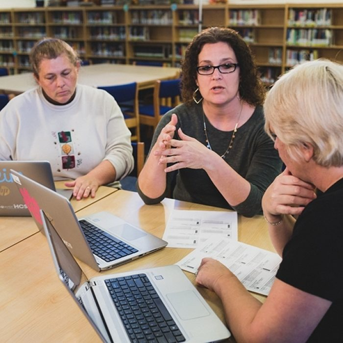 Three teachers sit at desk with laptops, speaking with each other as they work