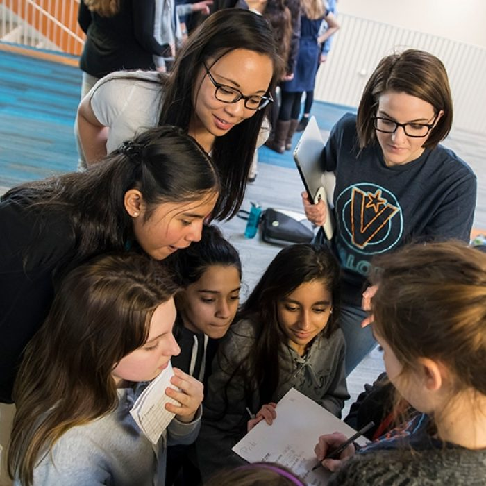 Students and teachers gather in a circle, looking down and smiling as one person writes on a paper.