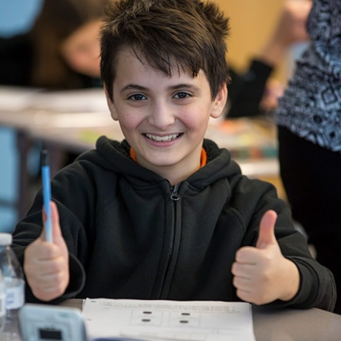Student sitting at desk gives two thumbs up, smiling