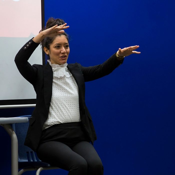 Woman in suit sits in front of white and blue background, gesturing enthusiastically
