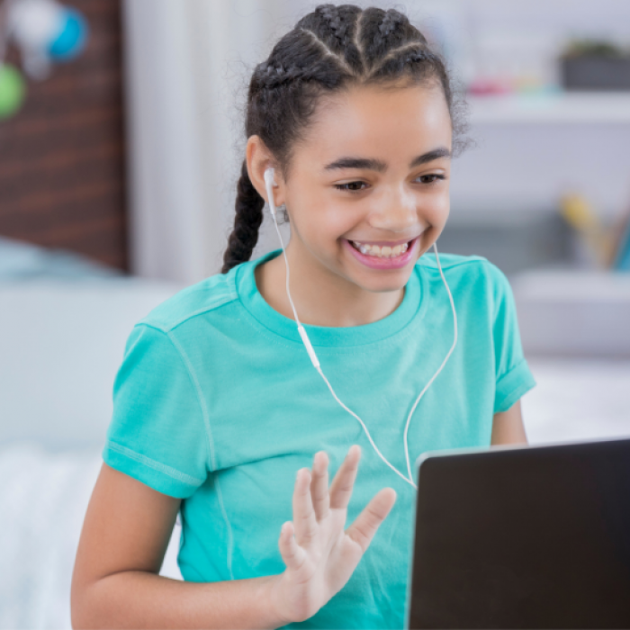 Student smiles at laptop screen, waving her hand, wearing earphones
