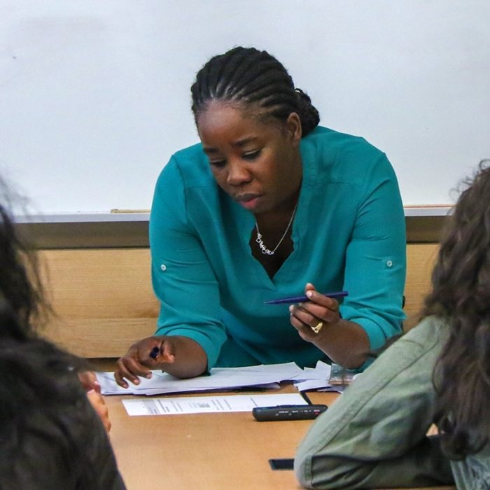 Teacher sitting at a desk with a small group of students looking at some papers with a pen in hand