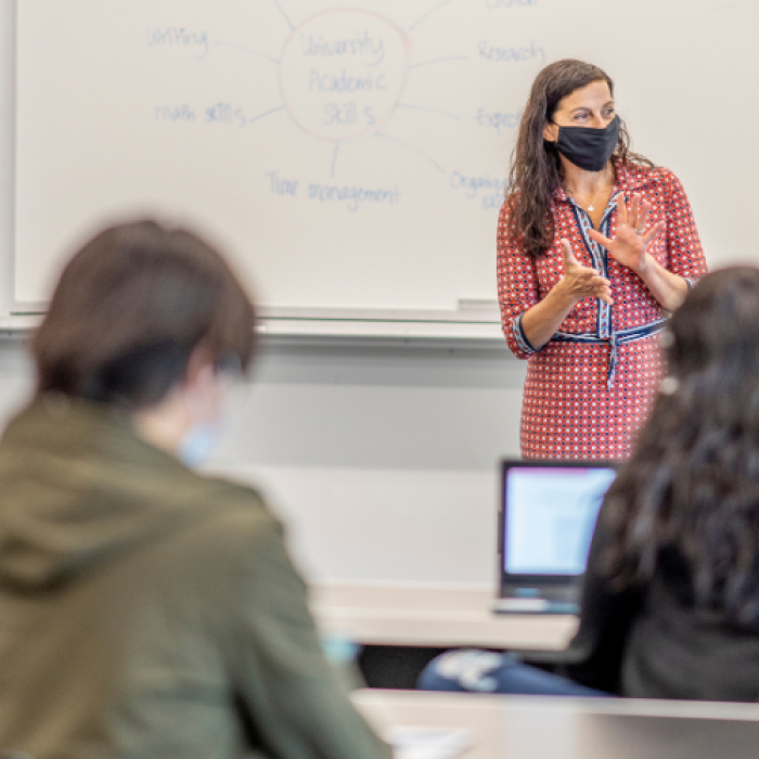 Teacher wearing mask stands in front of whiteboard in classroom as students sit scattered at desks, some with laptops in front of them, all wearing masks