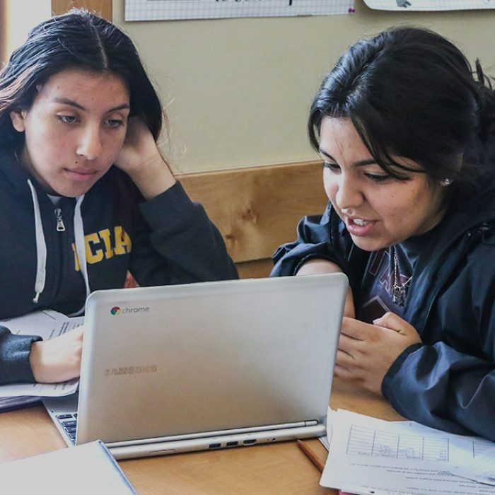 Two students look at laptop together