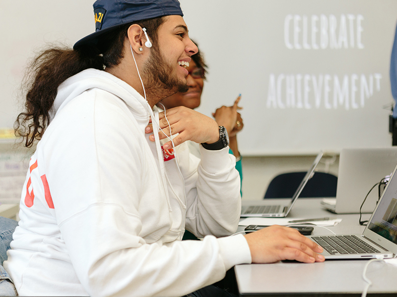 Student looks up from laptop smiling, talking