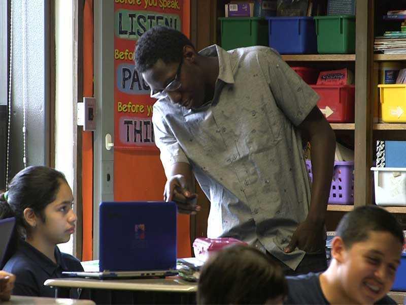 Photo of West Belden school badge and teacher with student
