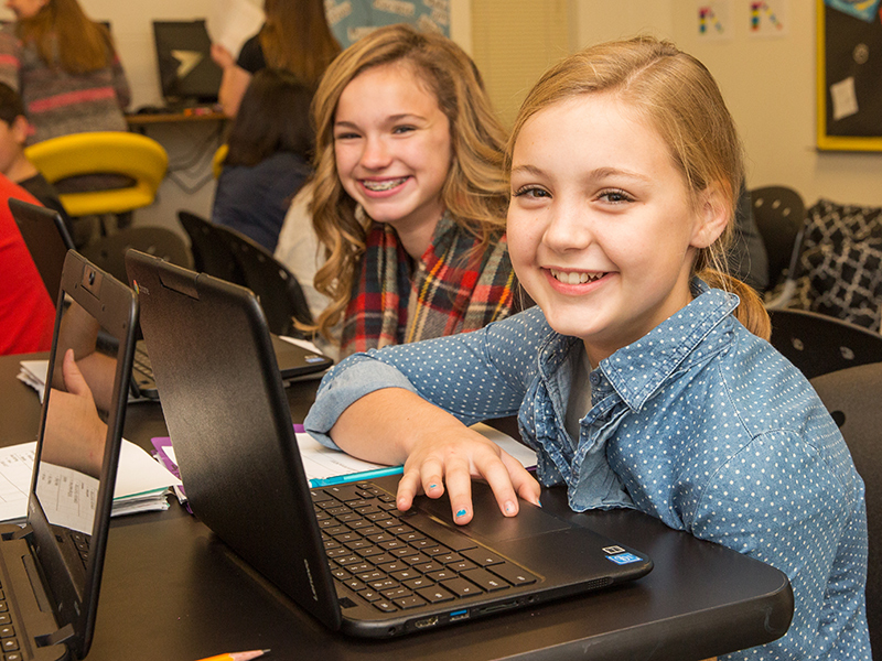 Students smile at camera while sitting at laptops