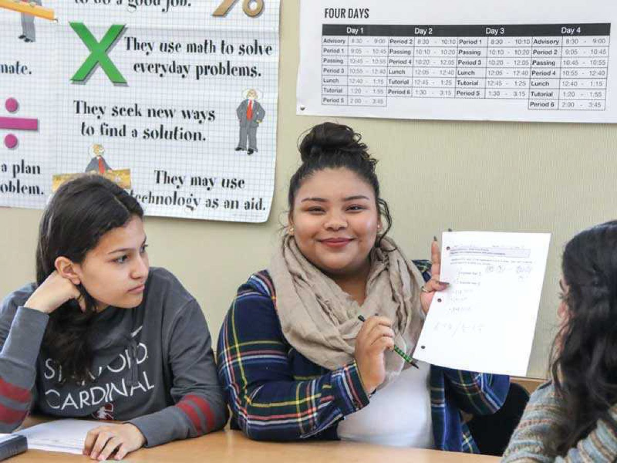 LPS student showing homework with other students looking on