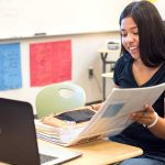 Photo of Lindsay student opening binder in front of laptop