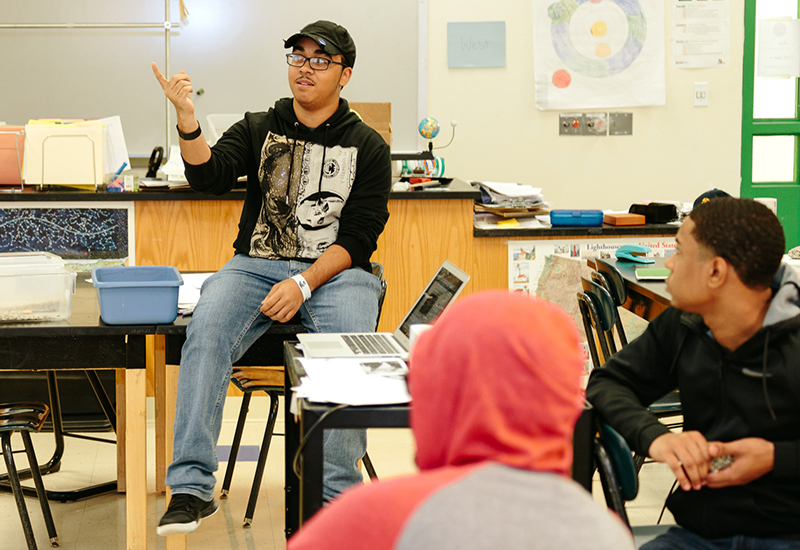 Student speaks, gesturing, while two students look on