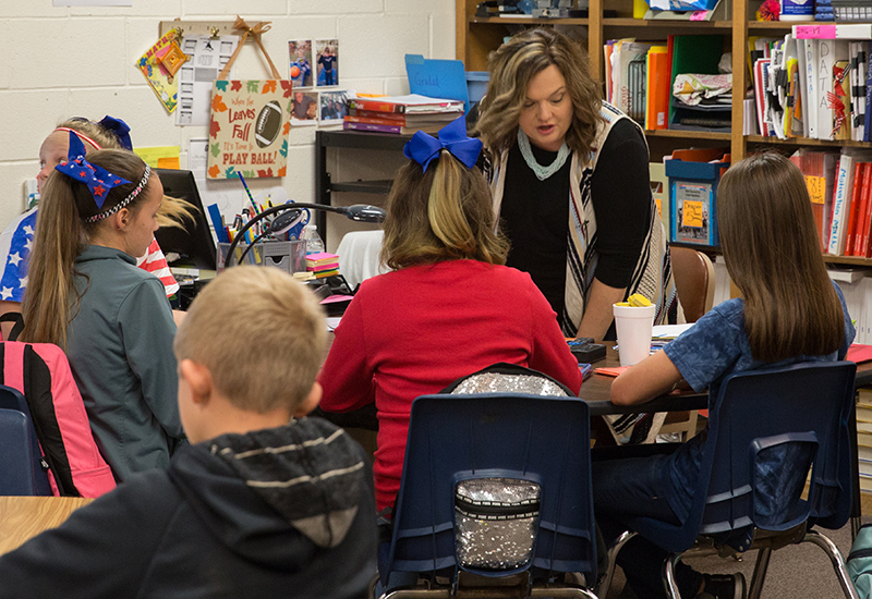 Teacher speaks with four students in a group at one table