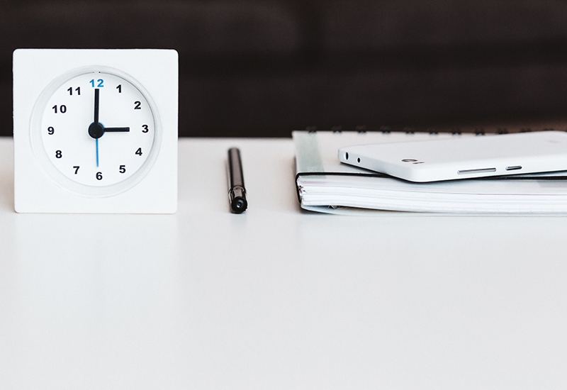 A clock, pen, and notebook lined up on a table