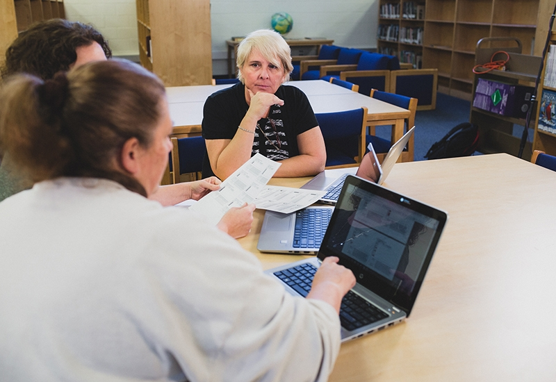 Three teachers sit at desk with laptops, holding papers, speaking with each other