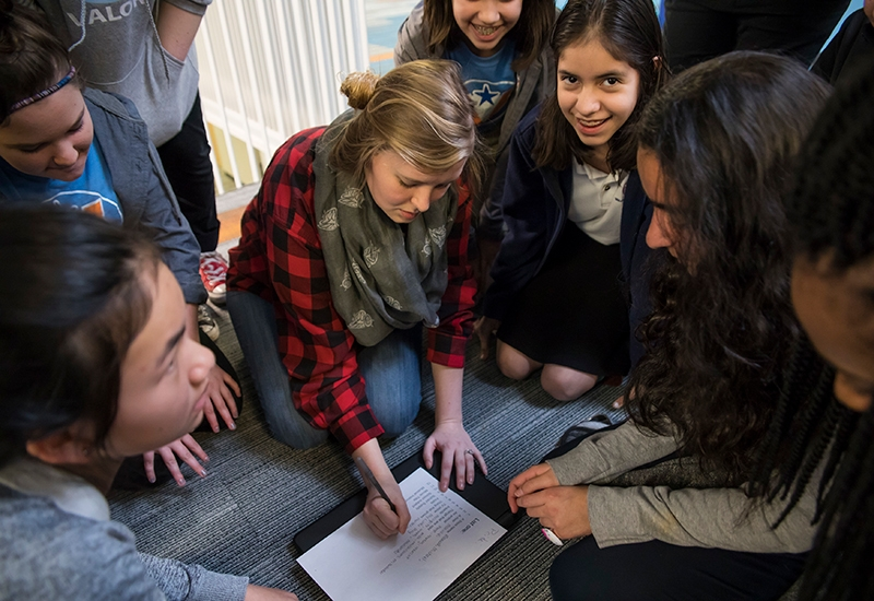 As teacher sits on the floor and writes on paper, students circle around her, looking down, while one student smiles at the camera