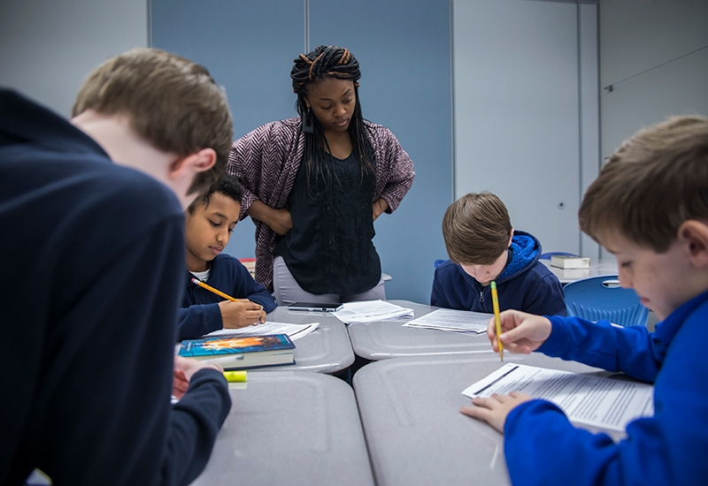 Teacher watches as students work at shared desks on paper