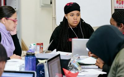 Student looks closely at another person at desk