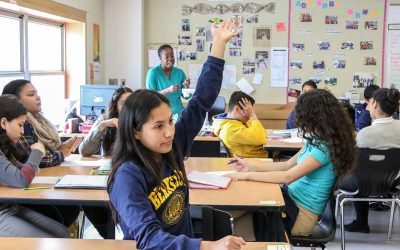 Photo of students and teacher in classroom with one student raising her hand