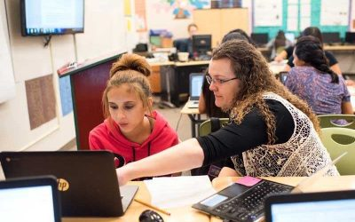 Photo of teacher and student working together in front of lap top