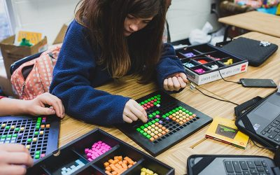 Student placing colorful blocks into black tray