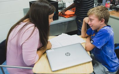 Student speaks with teacher, smiling
